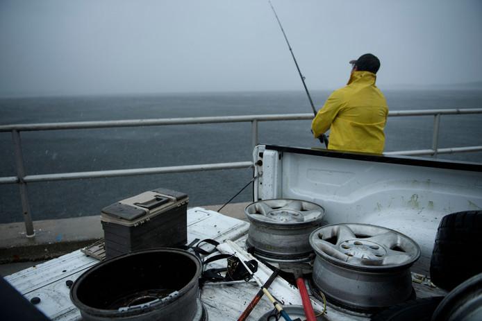 Een visser slaat zijn laatste vangst aan de haak voordat orkaan Michael aan land komt.