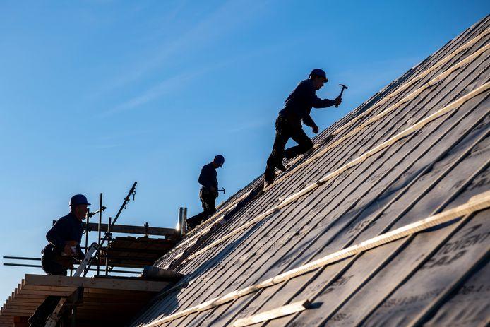 Werknemers van G. Kuijpers aan het werk aan een nieuwbouwhuis aan de Haarensebaan bij Udenhout.