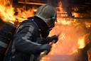 Een brandweerman is bezig met bluswerkzaamheden.