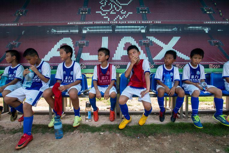 Kinderen rusten uit van de training bij de Guangzhou R&F voetbalacademie in Meizhou, het zuiden van China. Beeld AFP