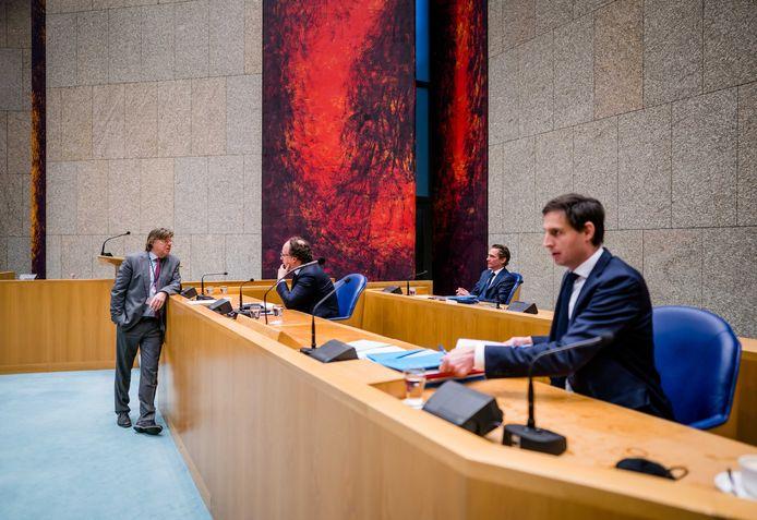 Tony van Dijck (PVV) heeft een onderonsje met minister Wouter Koolmees van Sociale Zaken en Werkgelegenheid tijdens een debat in de Tweede Kamer over de uitbreiding van het steunpakket voor bedrijven.