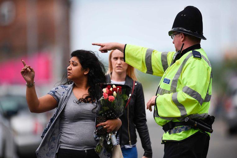 Een agent wijst een vrouw met bloemen naar de Manchester Arena. Beeld anp
