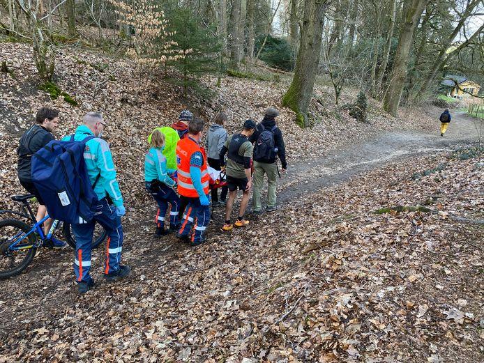 De gewonde mountainbiker (13) wordt vanuit het Ubbergse bos naar de ambulance gedragen.