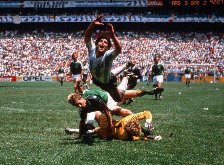 Diego Maradona valt over de Duitse Harald 'Toni' Schumacher (in het geel) en Karl-Heinz Förster (in het groen) tijdens de finale van het wereldkampioenschap op 29 juni 1986. Beeld BSR Agency