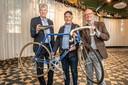 Sportschepen José Debels (CD&V) en Erik Lamsens van vzw Vrienden van KOERS samen met  Girowinnaar Johan De Muynck en de geschonken fiets.