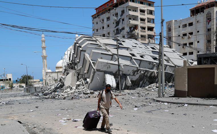 Een man loopt met een koffer langs een gebouw dat bij een Israëlisch bombardement is vernield.  Beeld AP