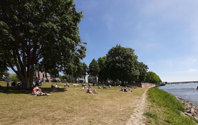 Op 'gepaste afstand' genieten veel mensen van de zon langs de IJssel in Deventer. Het is nergens stil langs de rivier.