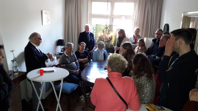 Een volle huiskamer hangt aan de lippen van Pim van Os (links), die als kleuter ondergedoken zat in Berghem.