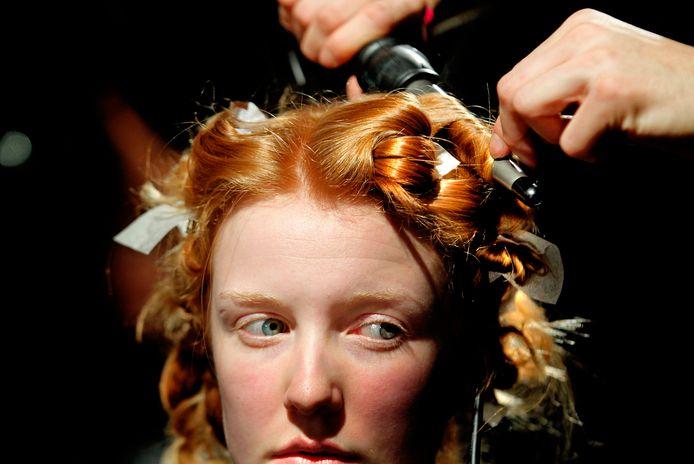 Het kapsel van een model wordt gedaan voorafgaand aan de opening van de Amsterdam Fashion Week: een te grote opgave voor wie thuis aan het knippen moet.