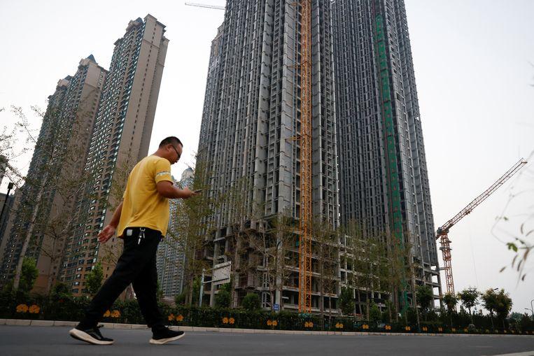 Een man wandelt voorbij onafgewerkte gebouwen ontwikkeld door Evergrande Group in Luoyang. Verschillende projecten van de vastgoedreus liggen stil. Beeld REUTERS