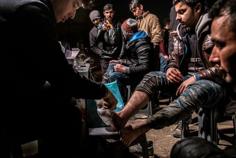 Migranten in het zelfgebouwde tentenkamp aan de spoorweg in Thessaloniki krijgen medische hulp van vrijwilligers. Beeld Joris van Gennip