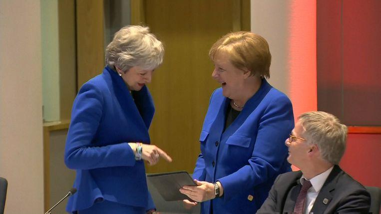 Premier May lacht met een foto die bondskanselier Merkel toont op haar iPad.