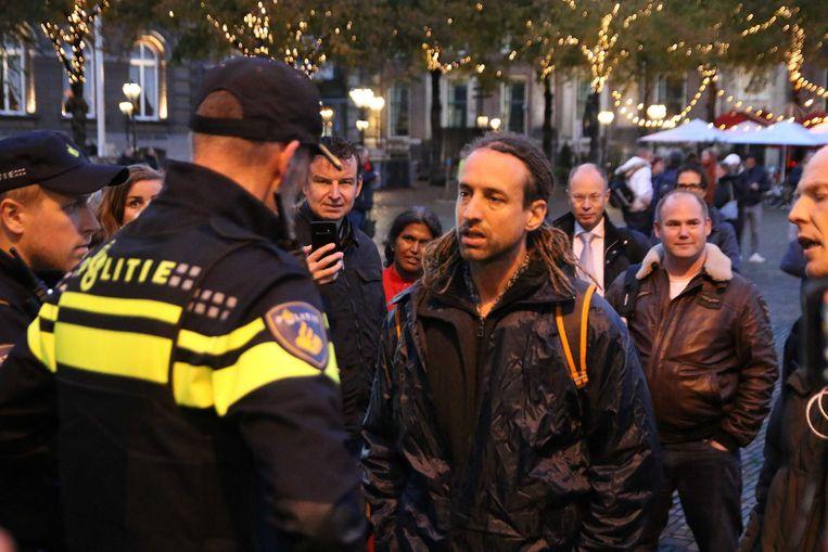 Willem Engel van actiegroep Viruswaarheid is in discussie met een politieagent tijdens een onaangekondigd protest. Beeld ANP