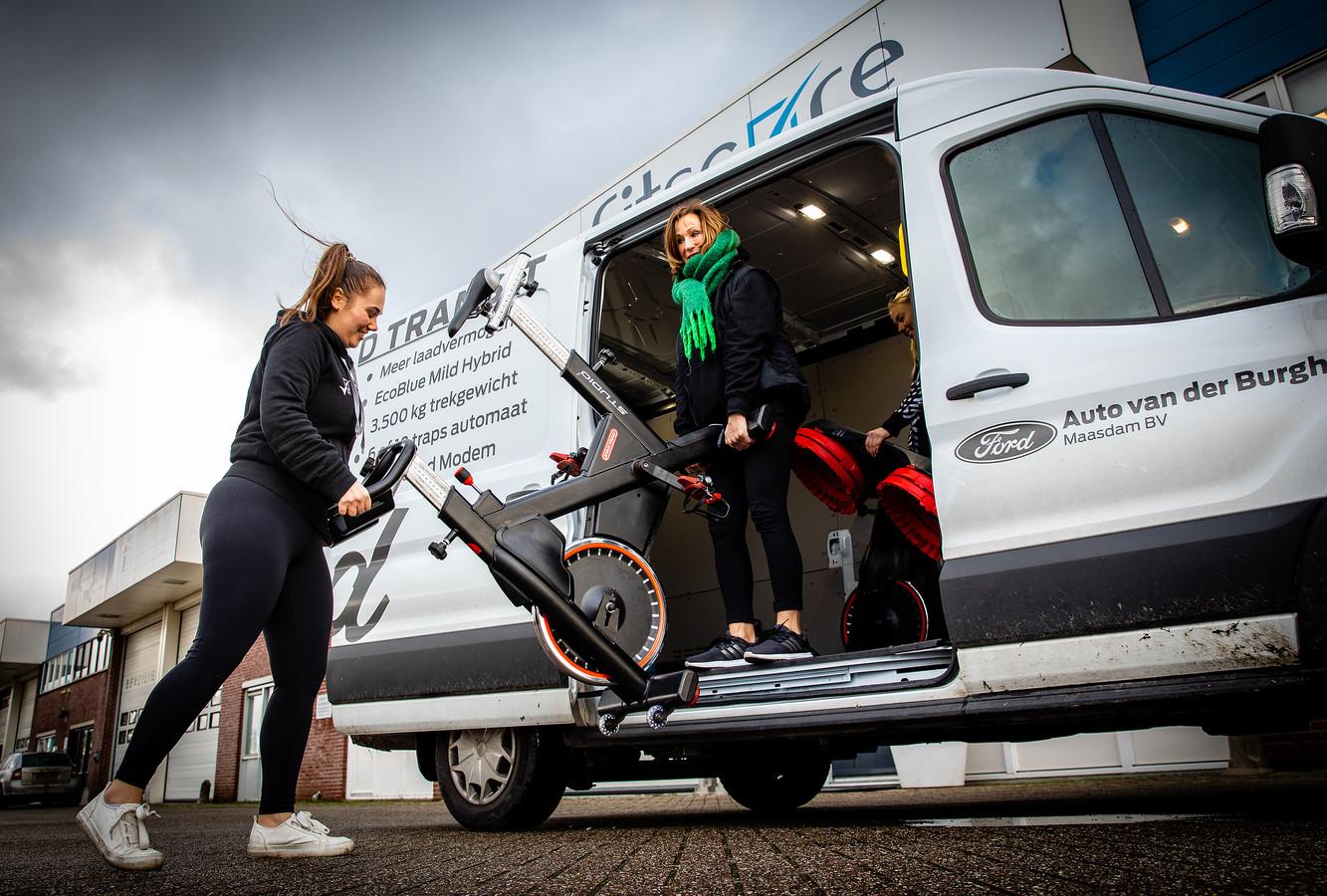Dochter Janniek Heijnen (30) en Philene van Essen (61) van Healthclub Fitscore in Strijen rijden twee keer per dag met de bus rond om leden fitnessapparaten te bezorgen.