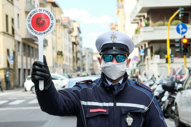 Een agent in Firenze (Italië) controleert voorbijgangers op niet-essientiële verplaatsingen.