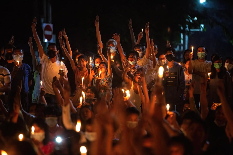 Demonstranten scanderen en protesteren tegen de junta met drie symbolisch opgestoken vingers in Yangon. Beeld Photo News