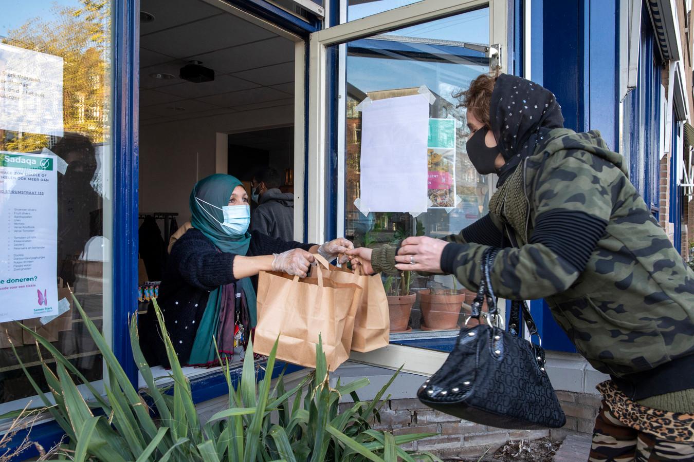 Darifa Benhadhoum deelt de tasjes met maaltijden uit. De hele maand wordt voor behoeftigen belangeloos gekookt.