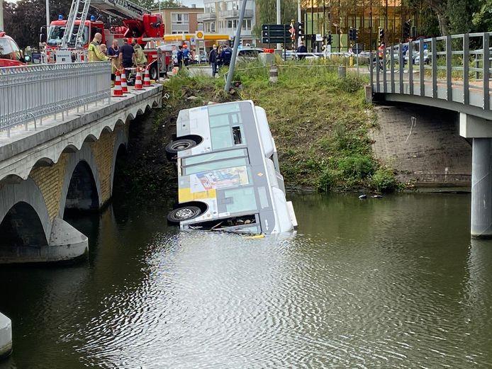 De bus ligt op zijn zijkant in het water.