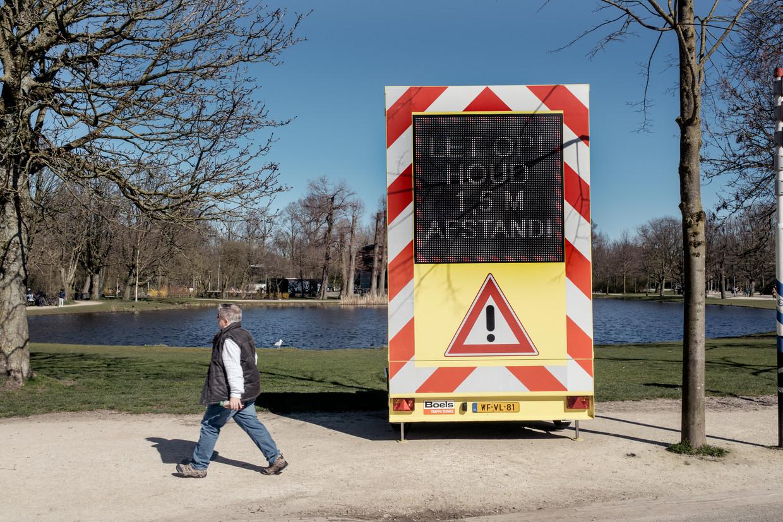 Een waarschuwingsbord om bezoekers van het Vondelpark te wijzen op de 1,5 meterregel. Beeld Jakob van Vliet