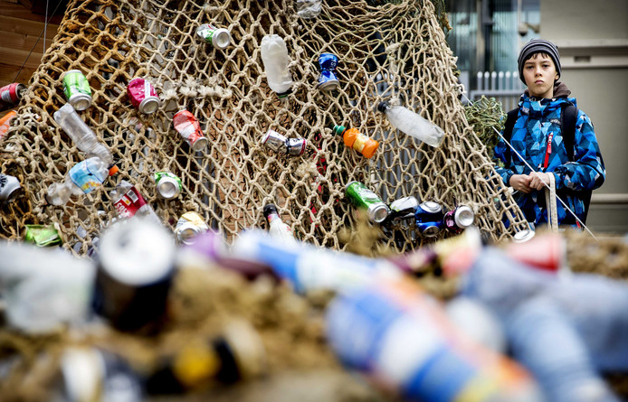 Actievoerders bij een standbeeld van Neptunus op het Plein bij de Tweede Kamer. De milieuorganisatie wil met de actie politici oproepen om statiegeld op kleine flesjes en blikjes in te voeren.