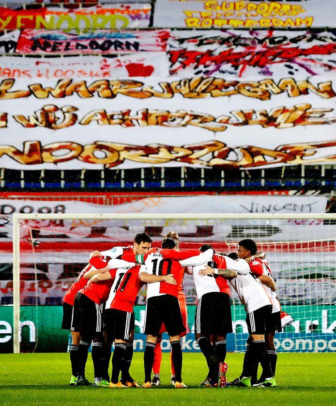 De spelers van Feyenoord met de spandoeken op de achtergrond.