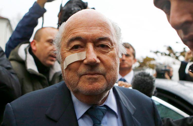 Een bebaarde Sepp Blatter verscheen met een gigantische pleister voor het TAS, waar hij bot ving Beeld AP