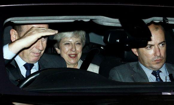 De Britse oud-premier Theresa May lacht breeduit terwijl ze zich laat wegrijden van de Houses of Parliament.