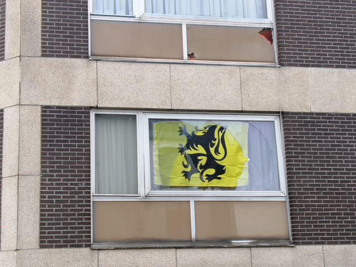 Raam ingegooid met oog op verwijderen van vlag. Bovenbuur heeft eveneens schade.