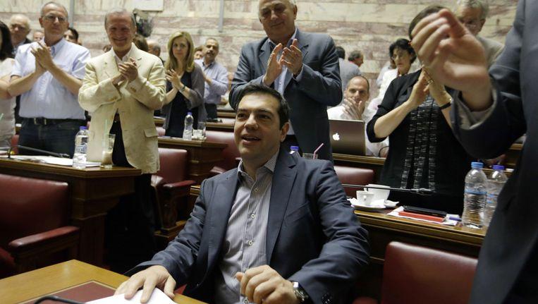 De Griekse premier Alexis Tsipras krijgt een applaus van zijn Syriza-partijgenoten bij binnenkomst van het parlement. Beeld AP