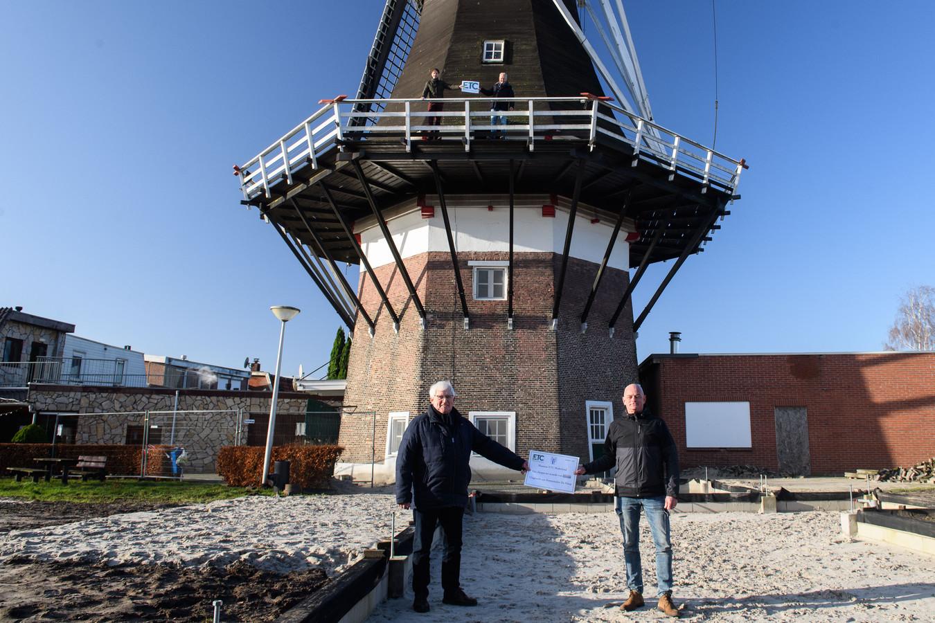 Gerard Pigge (l) ontvangt op de fundamenten van de molenschuur de symbolische cheque uit handen van Peter Pauelsen. Boven op de molen Michiel de Vries (l) en Bertus Tibben.