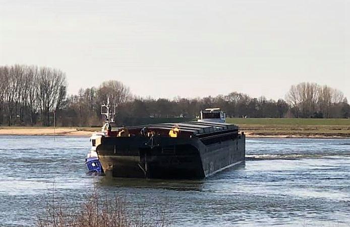 De duwboot dwars op de Waal bij Zaltbommel. Links is de politieboot nog net te zien.