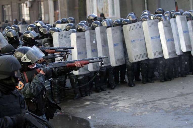 Politie richt op de demonstranten. Beeld afp