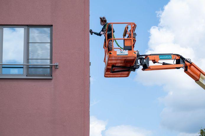 MECHELEN Gijs Vanhee legt de laatste hand aan zijn kunstwerk op een van de appartementsgebouwen op het Oud Oefenplein