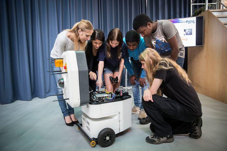 Deelnemers aan de Cyberwerkplaats buigen zich letterlijk over de opdracht: hack de robot. Beeld arie kievit