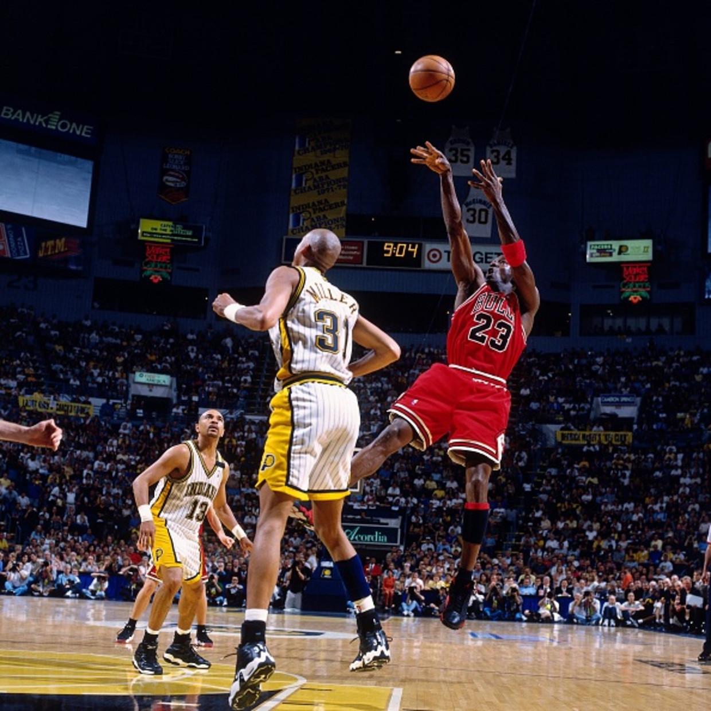 Michael Jordan hangt in de lucht voor zijn specialiteit, de zogeheten fadeaway. Bij die schotpoging stapt en springt hij achterwaarts, waarna hij de bal afvuurt.  Reggie Miller van de Indiana Pacers kijkt toe tijdens het duel in 1998.