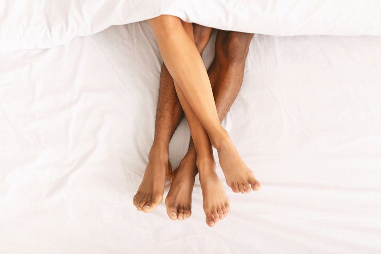 Family connection. Black naked male and female legs lying under duvet on bed, top view Beeld Getty Images/iStockphoto