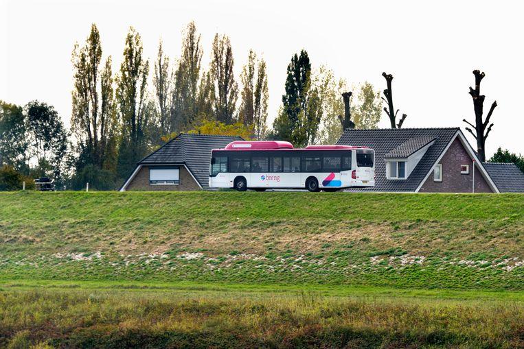Een passagiersbus van Breng rijdt over de dijk van de Ooijpolder bij Nijmegen. Beeld Flip Franssen
