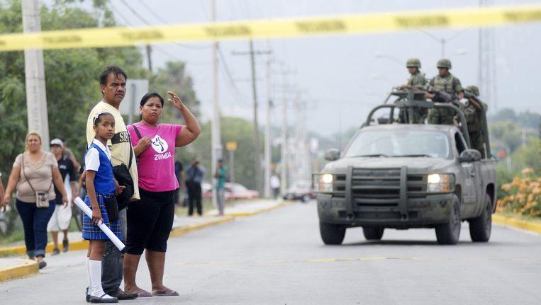 Voorbijgangers kijken toe terwijl soldaten arriveren op de plek van de schietpartij in Garcia.