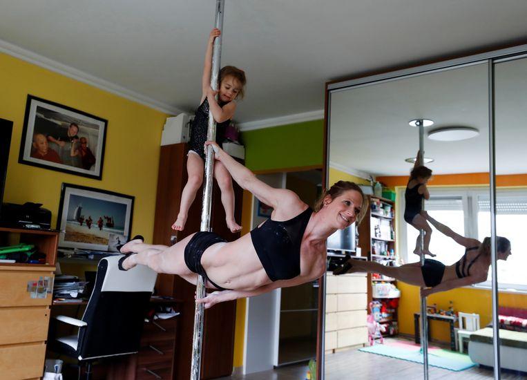 Als het niet kan zoals het moet, dan moet het maar zoals het kan. De Hongaarse paalacrobaat Kata Ott-Balogh, lid van circusgezelschap Taurin, oefent haar kunsten thuis in Boedapest. Dochtertje Tetisz doet vrolijk mee. Beeld REUTERS