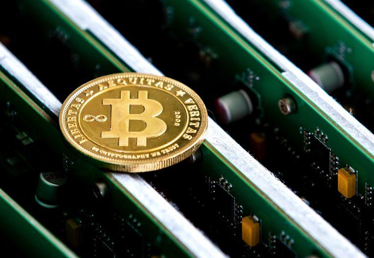 Een munt met daarop het bitcoinlogo op het kantoor van Bitonic, een bedrijf dat euro's omwisselt in bitcoins of andere cryptovaluta. Beeld ANP