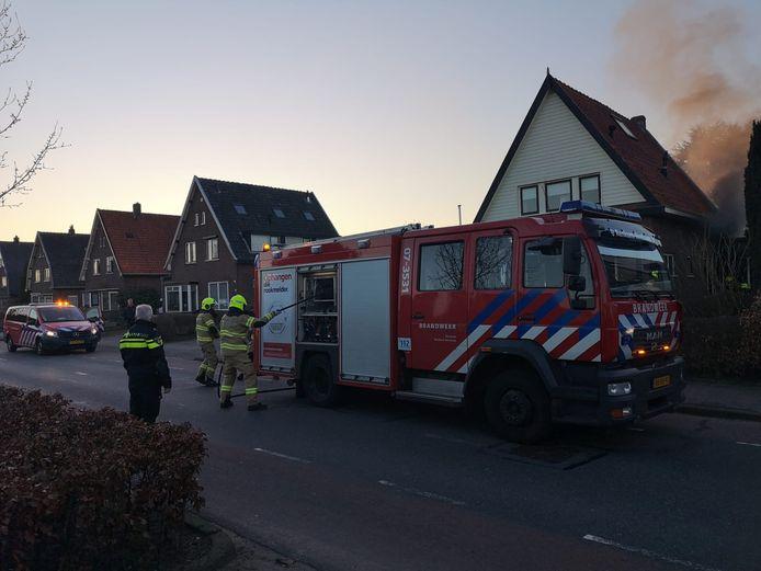 Uit de woning in Renkum komt rook door brand in de keuken. Brandweer staat op het punt het vuur te blussen.