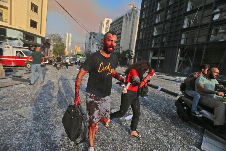 Gewonde inwoners lopen weg van de explosie. Beeld AFP
