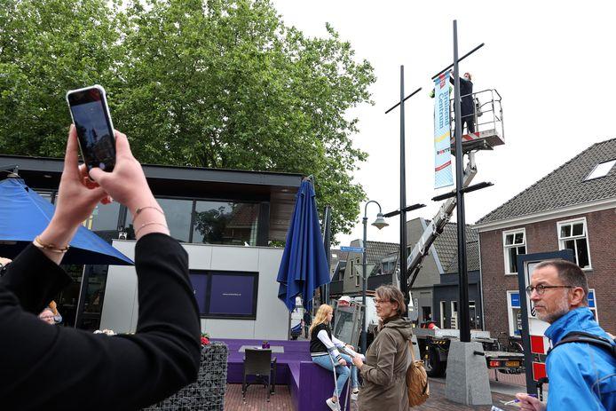 Wethouder Van Alpen hangt een banier op als symbool voor de heropening van de opgeknapte Rechterstraat in Boxtel.