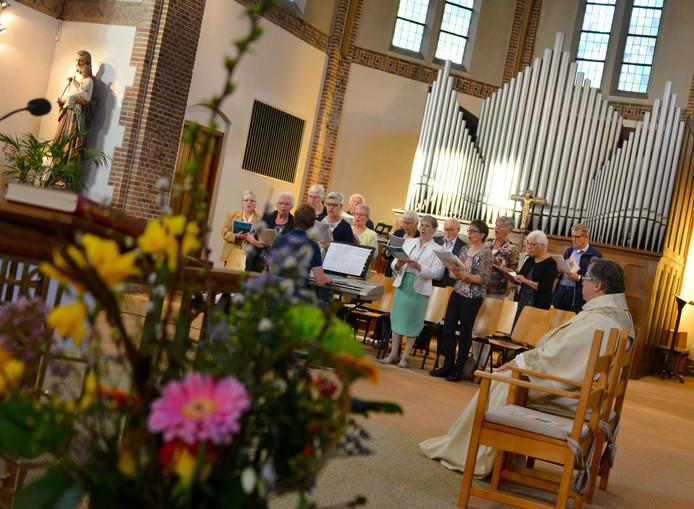 Pastoor Paul Janssen luistert naar het kerkkoor. Archieffoto Nienke van de Kruijs