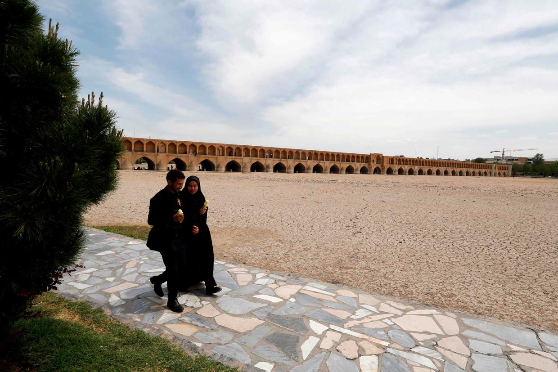 Iraniërs lopen bij een brug over een drooggevallen rivier in de stad Isfahan.  Beeld Hollandse Hoogte / AFP