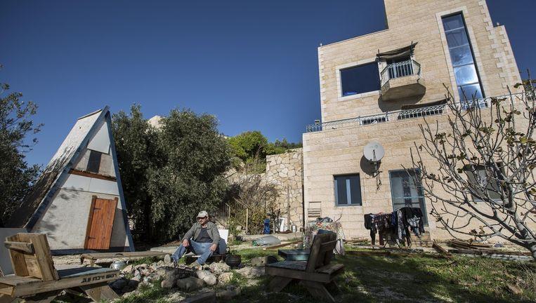 Een bewoner zit bij zijn huis dat op Airbnb staat. De woningsite kwam afgelopen weken onder vuur te liggen nadat de appartementen in nederzettingen waren ontdekt. Beeld ap