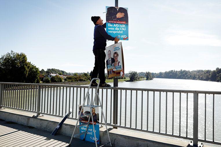 Heinricht Kraft, brandweerman in het stadje Marktl, bevestigt aan elke lantaarnpaal een AfD-poster. Beeld Daniel Rosenthal