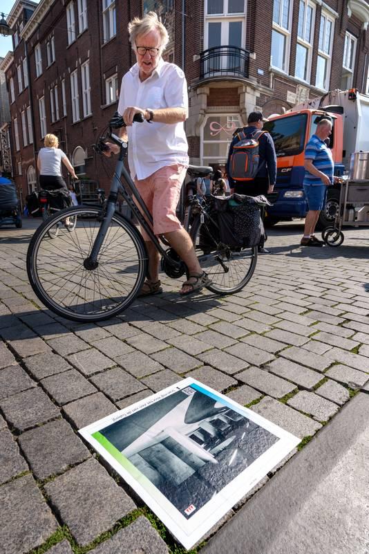 Een vrouw  bekijkt één van de opvallende stoeptegel-stickers op de Markt in Den Bosch.