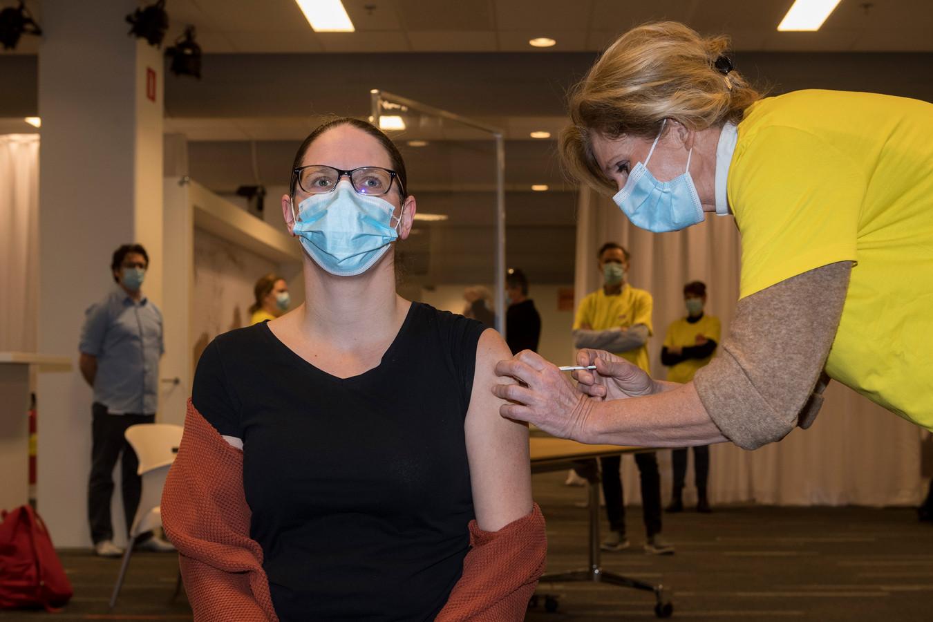 Danielle Volman van zorginstelling Pleyade krijgt als eerste het vaccin toegediend in de vaccinatielocatie van de GGD op Papendal bij Arnhem.