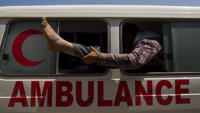 Een rebel houdt het been vast van een gewonde, terwijl ze aankomen bij een kliniek vlakbij misurata. Beeld ap